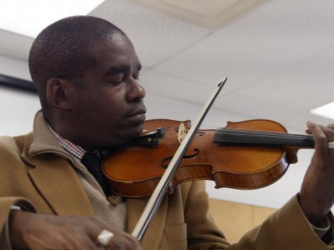Derek Reeves demonstrates viola at Scarboro Center